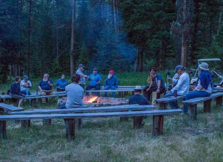 Some people visit around a campfire.