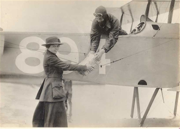 Smiling man and woman exchange a package beside an aircraft in 19191, an image for the return policy at This House of Books, the community-owned independent bookstore and tea shop in downtown Billings, Montana